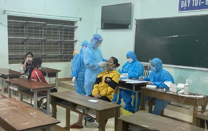 Lực lượng y tế lấy mẫu xét nghiệm cho học sinh trường Phổ thông Dân tộc Bán trú và Trung học cơ sở Phước Chánh tối 12/10. Ảnh: Đắc Thành.