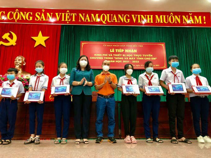Trang, Quyên, Vũ (học sinh áo trắng đứng thứ 4, 5, 6 từ trái sang) nhận máy tính bảng hỗ trợ học trực tuyến từ quỹ Hy vọng và FPT. Ảnh: Vũ Lộc.